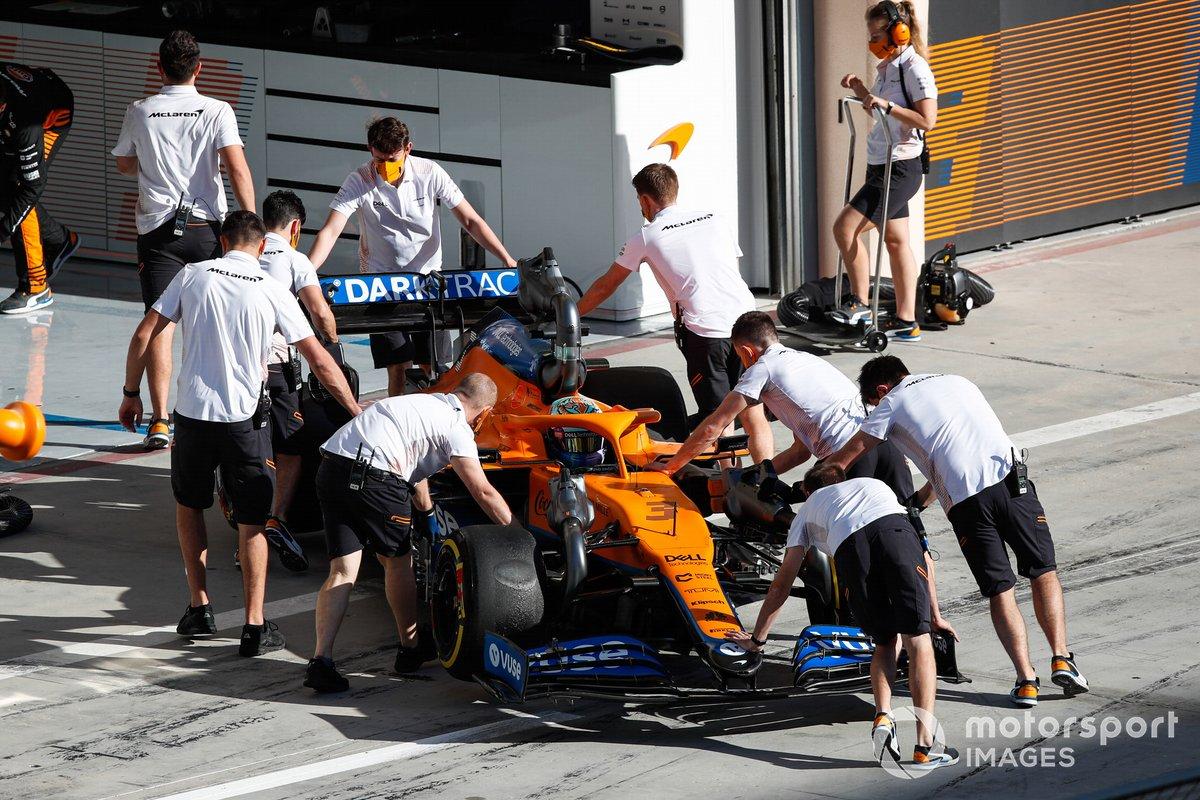Mecánicos empujan el coche de Daniel Ricciardo, McLaren MCL35M, hacia el garaje.