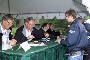 Don Nicholson, Dan Gurney, Sir Jackie Stewart and Lyn St. James sign some autographs for a few fans