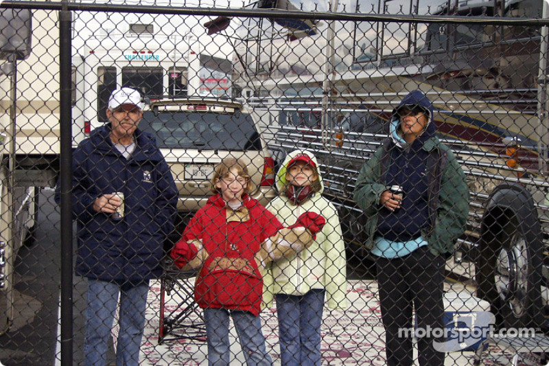 Even the fence does not keep people from enjoying the race