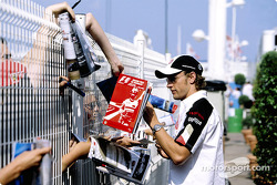 Jenson Button signs autographs