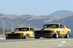 #15 1970 Boss 302 Mustang and the #16 Boss 302 Mustang enter the braking zone for turn 8 side by side