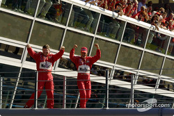 Race winner Michael Schumacher and Ross Brawn celebrate on their way to the podium