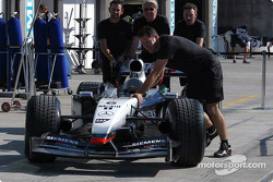 McLaren team members push car on pitlane