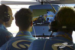 Renault team members watch Fernando Alonso qualifies