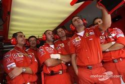 Ferrari team members watch Rubens Barrichello qualifying lap
