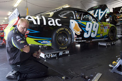 A crew member works on the No. 99 Aflac Ford