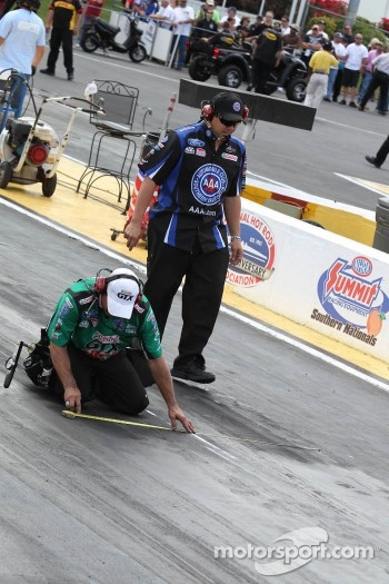 John Force Racing crew members inspecting the track before Roberts Hight's 1st round elimination