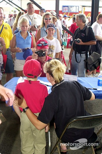 Sarah Fisher poses with a fan during the autograph session