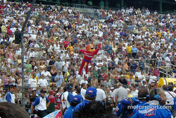 Guy in corny mascot suit inspiring a large crowd of people to yell