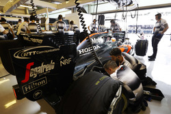 The team work on the car of Fernando Alonso, McLaren in the garage.