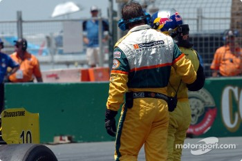 A.J. Allmendinger is escorted from the track after hitting the tyre wall on the end of the beach chicane