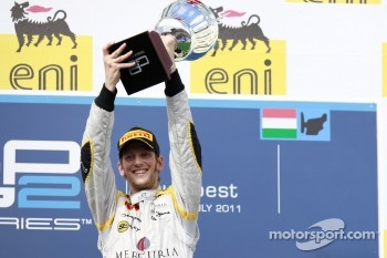 Romain Grosjean celebrates his fifth feature race win of the season on the podium