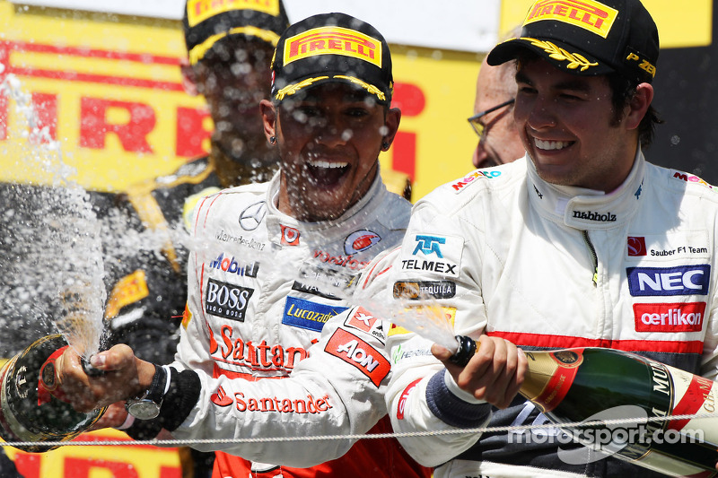 Race winner Lewis Hamilton, McLaren Mercedes celebrates on the podium with Sergio Perez, Sauber