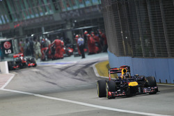 Sebastian Vettel, Red Bull Racing leads Jenson Button, McLaren out of the pits
