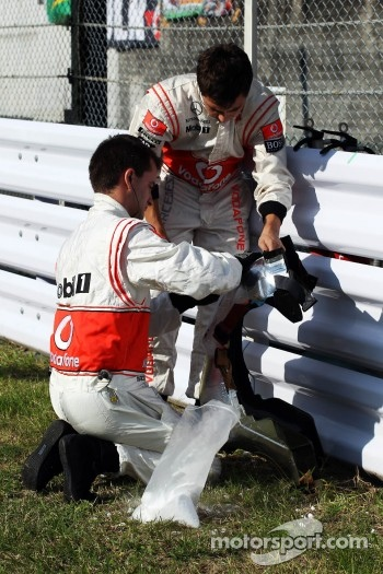 McLaren mechanics with a race seat on the grid
