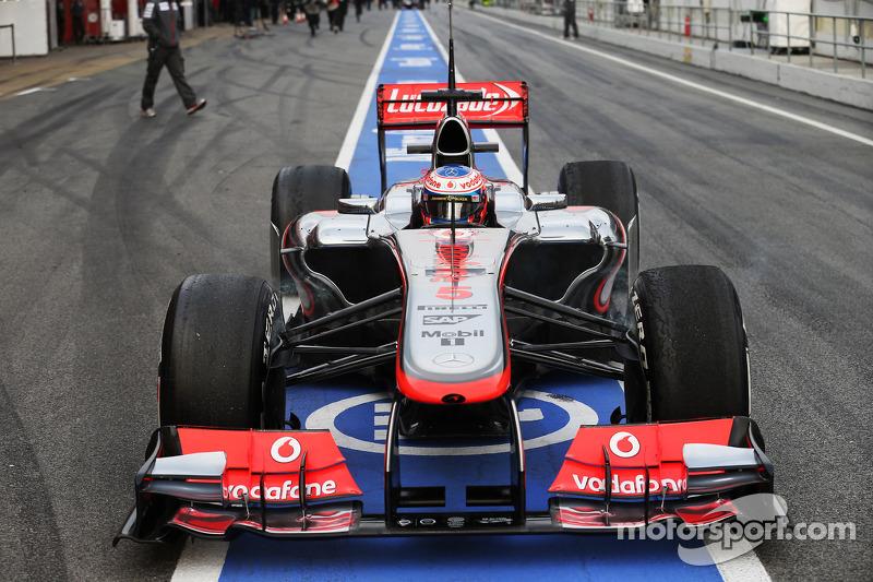 Jenson Button, McLaren MP4-28 stops in the pit lane