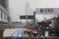 Sergio Perez, McLaren MP4-28 and Jenson Button, McLaren MP4-28 leave the pits