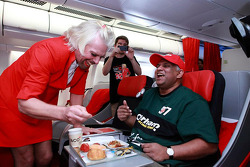 Sir Richard Branson serves as a flight attendant on Air Asia flight after losing a bet with Caterham F1 boss Tony Fernandes