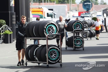Pirelli tyres pushed on a trolley by a Mercedes AMG F1 mechanic