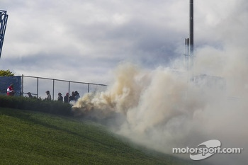 A fire on the grass near the track