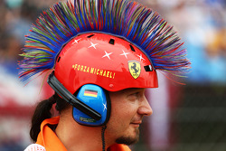 A marshal with a mohican Michael Schumacher, themed  helmet.