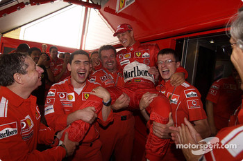 Michael Schumacher celebrates with Ferrari team members