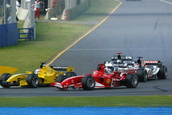 First corner action: Michael Schumacher battles with Narain Karthikeyan