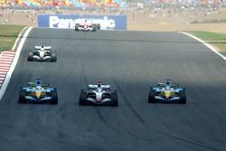 Kimi Raikkonen passes Giancarlo Fisichella while Fernando Alonso watches the action