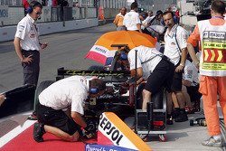 Crew members work on the car of Borja Garcia