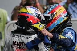 Race winner Juan Pablo Montoya celebrates with Fernando Alonso