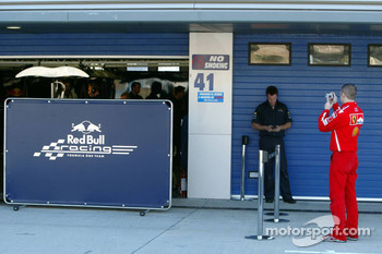 A Ferrari team member takes a picture of the Red Bull Racing garage