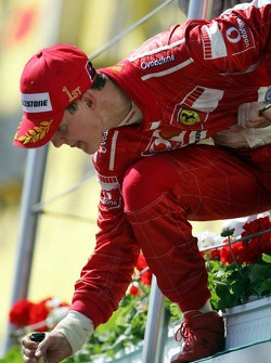 Michael Schumacher drops a bottle a champagne to his team