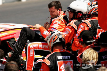 Crew members assist Tony Stewart as he climbs from his No. 20 Home Depot Chevrolet