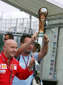 Italian Ferrari team members enter the paddock holding up a dummy football World Cup trophy