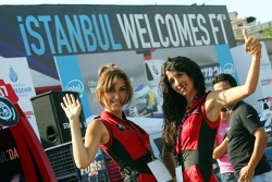 Girls pose in front of an advertising banner in downtown Istanbul