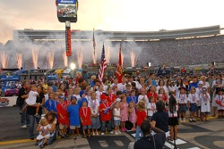 Kids of drivers and crew members gather to sign the national anthem