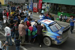 Petter Solberg and Phil Mills mobbed by fans on the way to the service park