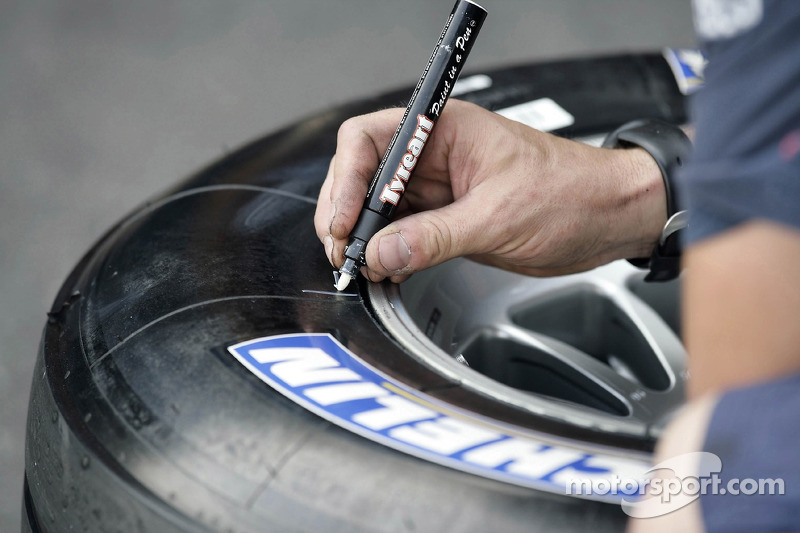A Red Bull Racing crew member marking Michelin tyres