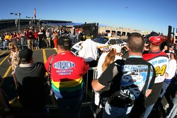 Fans watch the cars as they head to the track for the start of the session