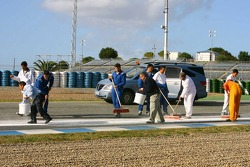 Track staff clean up the oil left after Kazuki Nakajima's engine failure