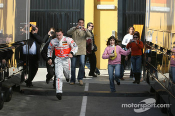 Fernando Alonso runs from the garage to the hospitality