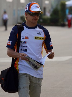 Heikki Kovalainen, Renault F1 Team arrives at the track and reads The Red Bulletin