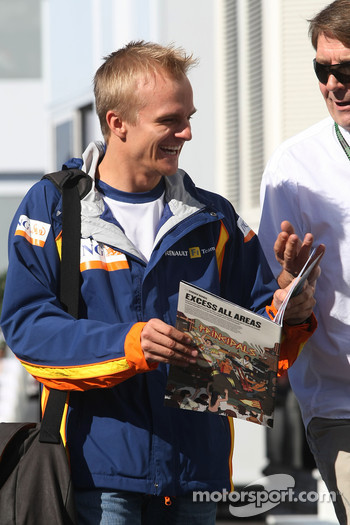 Heikki Kovalainen, Renault F1 Team, laughs while reading the Red Bulletin