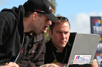 i-MOTO Racing team members watch qualifying as Nick Wittmer is fastest