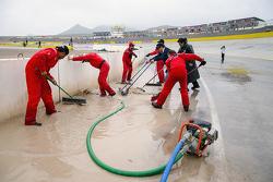 Oficiales de pista limpian el agua acumulada por la lluvia