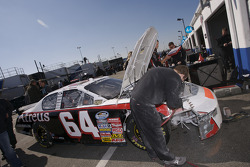 A crew member works on the damaged car of David Stremme