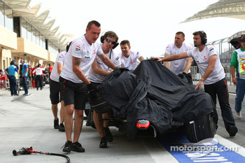 Lewis Hamilton's, McLaren Mercedes is pushed back to the garage by his mechanics after Lewis's crash