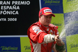 Podium: race winner Kimi Raikkonen sprays champagne