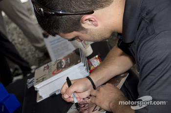 Reed Sorenson sings a couple autographs for his fans during an appearance