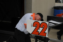 A crew member works on Davey Hamilton's rear wing